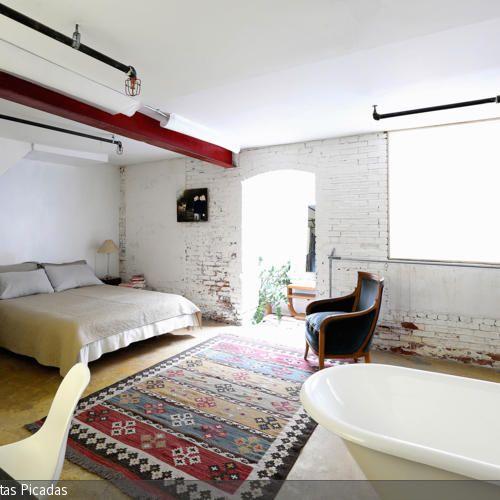 Die Wohnidee im Industrie-Stil vereint ein Doppelbett, eine offene Badewanne und eine Arbeitsfläche in einem Raum.  - mehr auf roomido.com