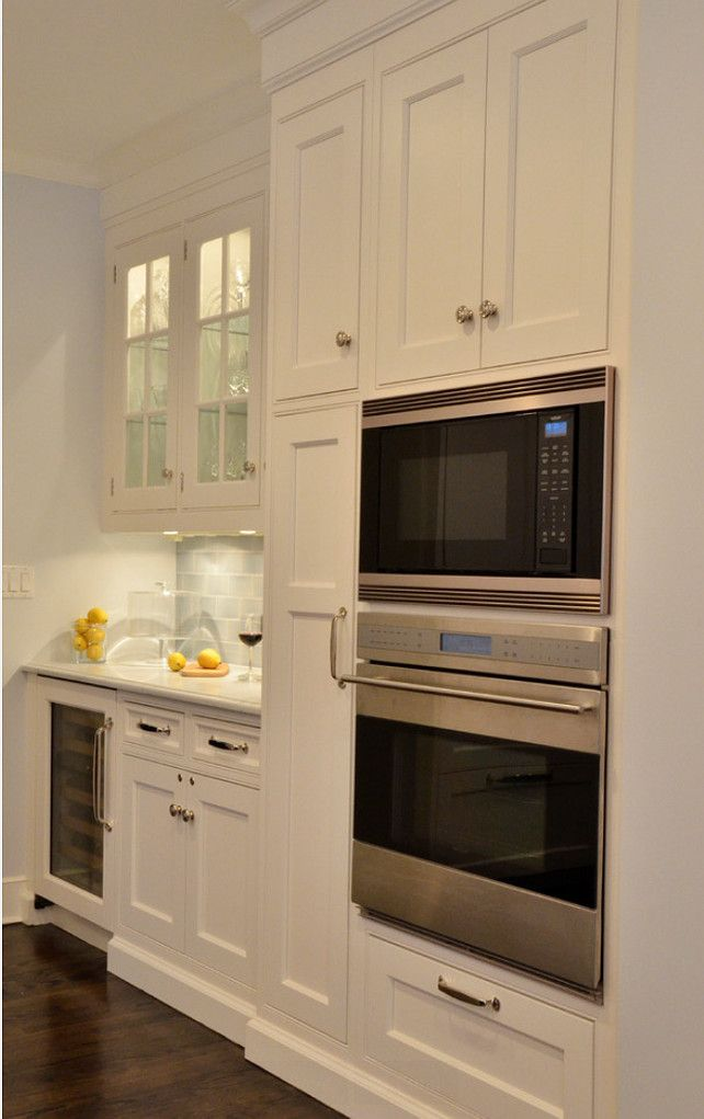 Kitchen Cabinet Ideas. Next to the the oven and microwave, a tall broom cabinet houses cleaning gear. #Kitchen #KitchenCabinet