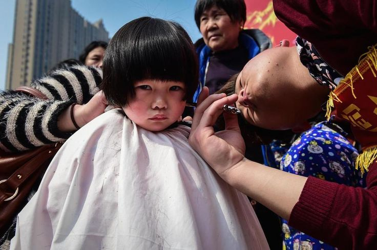 A child has a free haircut for good luck in Hefei, capital of east China's Anhui Province, on the second day of the second month in traditional Chinese lunar calendar. [980x652] Photo by Du Yu
