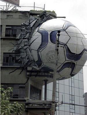 Campanha da Nike promovendo a Copa do mundo. Bola gigante dando a impressão de que destruiu parte da fachada do prédio.