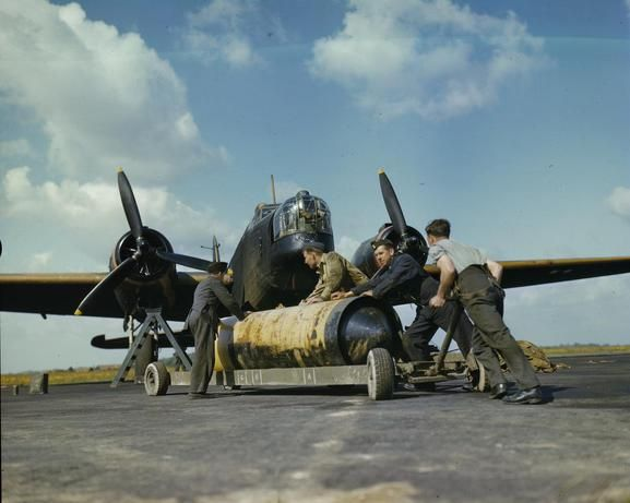 THE ROYAL AIR FORCE IN BRITAIN, MAY 1942. Royal Air Force ground crew push a 4,000lb blast bomb towards the bay of a Vickers Wellington bomber of No 419 Squadron, Royal Air Force at Mildenhall.