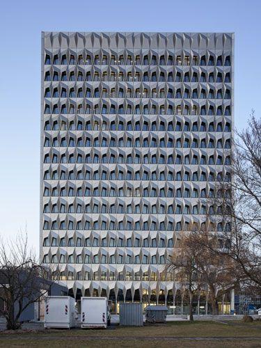 <p>Die markanten  Sonnenschutzelemente aus eloxiertem Aluminiumblech sind Teil der  geschosshohen Fassadenbekleidung und falten sich – wo erforderlich –  entsprechend aus. Ihre geometrische Ausgestaltung basiert auf komplexen Simulationen und wurde in Zusammenarbeit mit Transsolar entwickelt. Erreicht wird ein Optimum zwischen Tagesbelichtung und Sonnenschutz. Die 1,87 x 3,87 Meter großen eloxierten Aluminiumelemente sind vorgefertigt und an der Unterkonstruktion der VHF mittels Agraffen ...