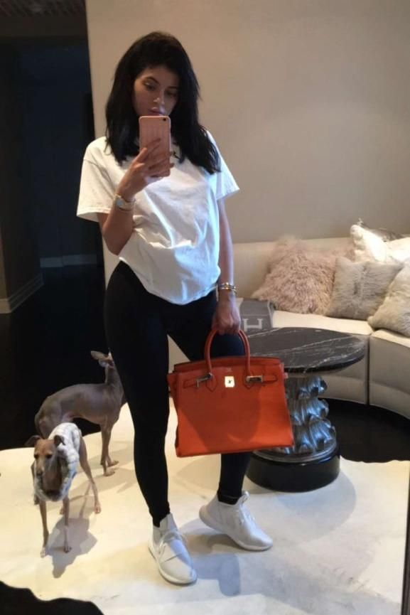Kylie Jenner wearing Hermes Birkin Bag in Orange, Ovo 1-800-Hotlinebling Iphone Case and Adidas Tubular Defiant Shoes in Core White