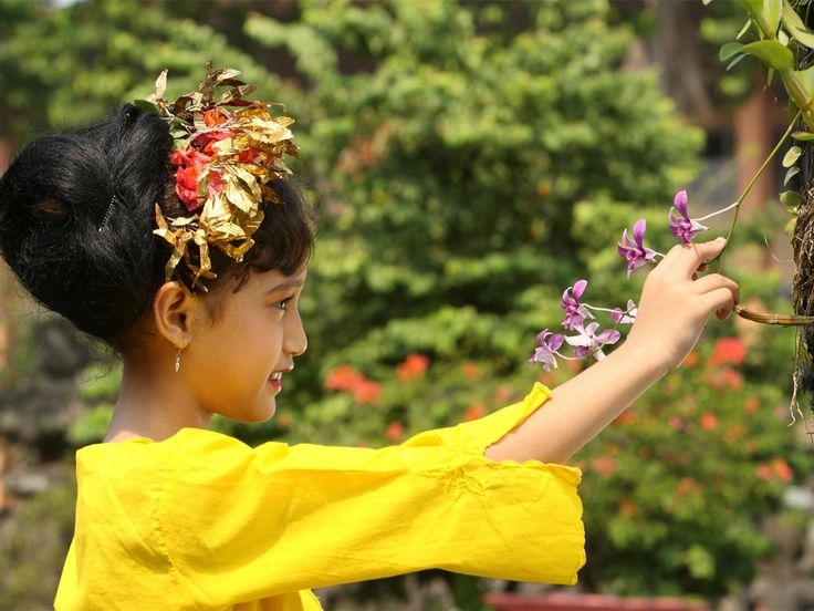 A Balinese girl -- donned in traditional dress -- picks a flower.