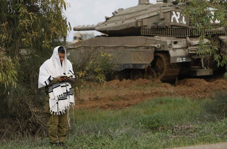 IDF soldier praying by tank.