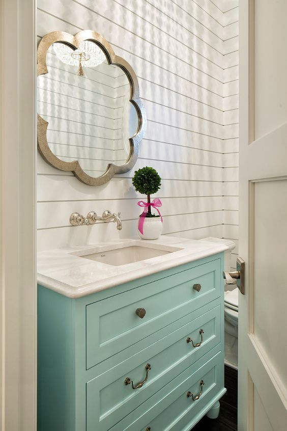 Bathroom with turquoise vanity and shiplap walls.