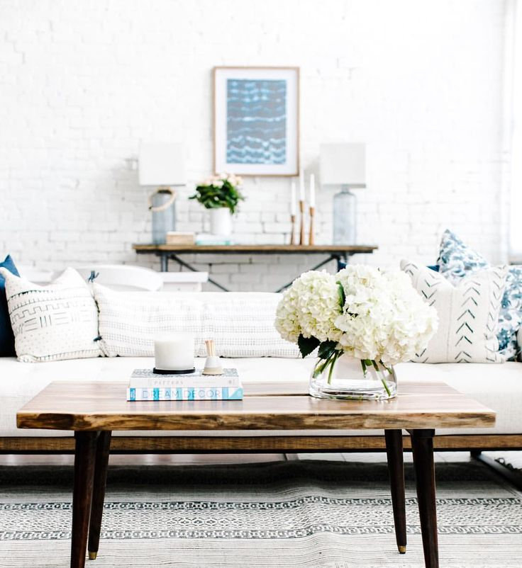 Bright and airy living room with white expose brick, white linen and wood sofa, Studio McGee pillows, white hydrangeas and blue ikat print.