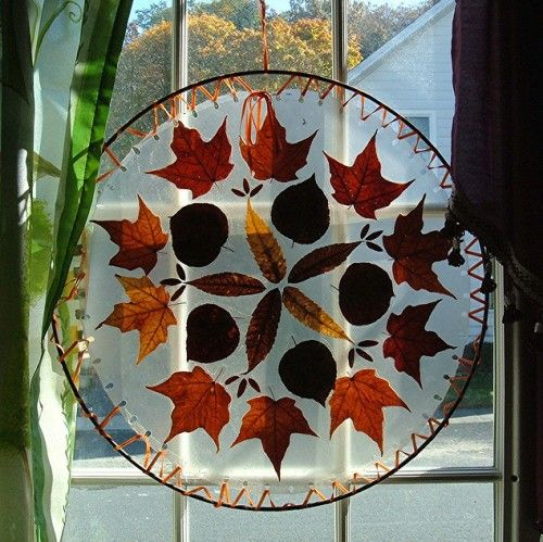 Placed between two sheets of contact paper, this fall art allows orange and red light to filter through the window. Cut contact paper into circles, sandwich the leaves between, and punch holes around the edge. Carrington laced orange satin ribbon through the holes, attaching the contact paper to a metal ring.