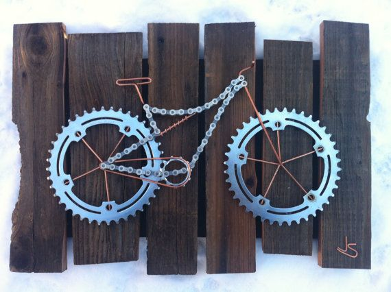 Bike art created by combining used bike components, copper leftover from a solar array, and old cedar fencing to resemble a mountain bike. A dog