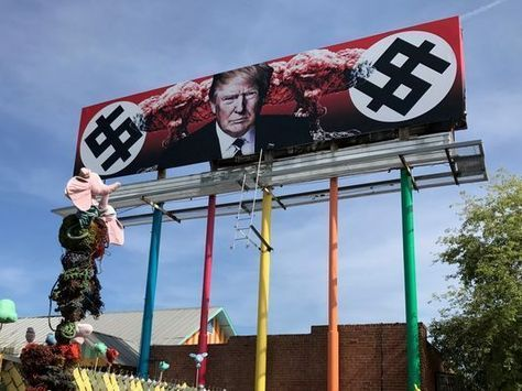 A billboard depicting President Donald Trump's face next to explosions and dollar signs created with typography imitating Nazi swastikas went up in downtown Phoenix on Friday afternoon.