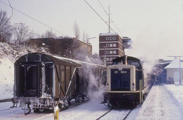 Es waren harte Wintertage im Jahr 1987. Am 13.1.1987 sieht man das deutlich am Rollmaterial der Bundesbahn im Hauptbahnhof Osnabrück. Neben dem Behelfspackwagen steht um 13.31 Uhr abfahrbereit 211015 mit dem Nahverkehrszug nach Bramsche.