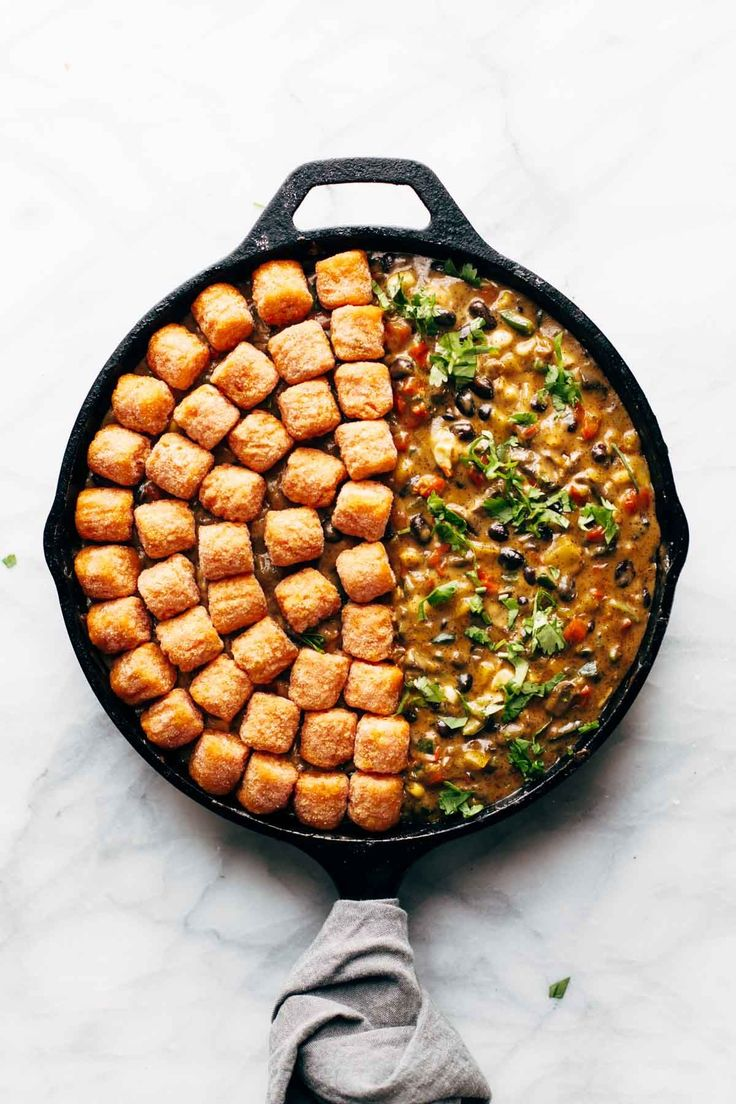 This sweet potato tater tot hotdish is a spicy twist on the original - loaded with peppers, corn, black beans, homemade queso sauce, and tots! YUM! Sponsored by @LodgeCastIron | pinchofyum.com