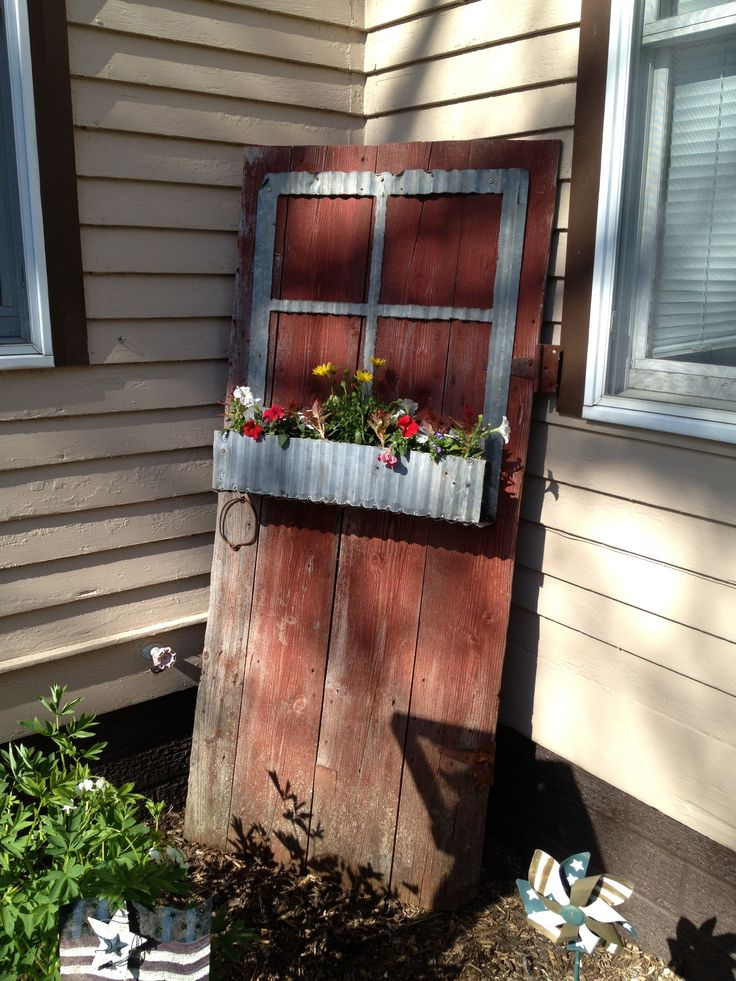 Vintage barn door with corrugated tin siding flower box