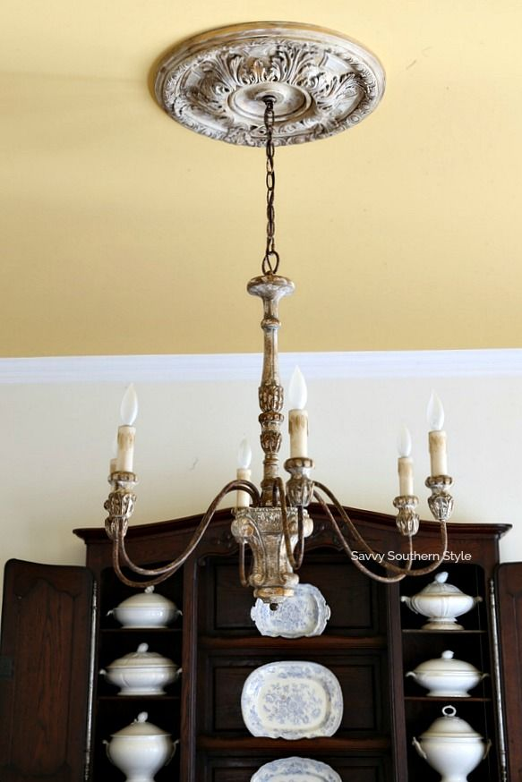 french country chandelier and hutch filled with ironstone