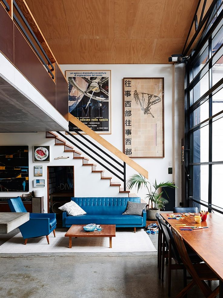 Gorgeous mid-century living room with oversized artwork on the walls, concrete floors, cobalt blue walls and black railings and seating   Photos by Eve Wilson