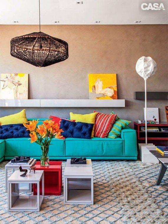 Quando a base é neutra, os móveis e acessórios podem ser bem coloridos. O tapete básico e a parede de cimento queimado permitiram que o sofá turquesa brilhasse na companhia das almofadas coloridas. Tem vermelho, amarelo, azul marinho, tudo em perfeita harmonia.