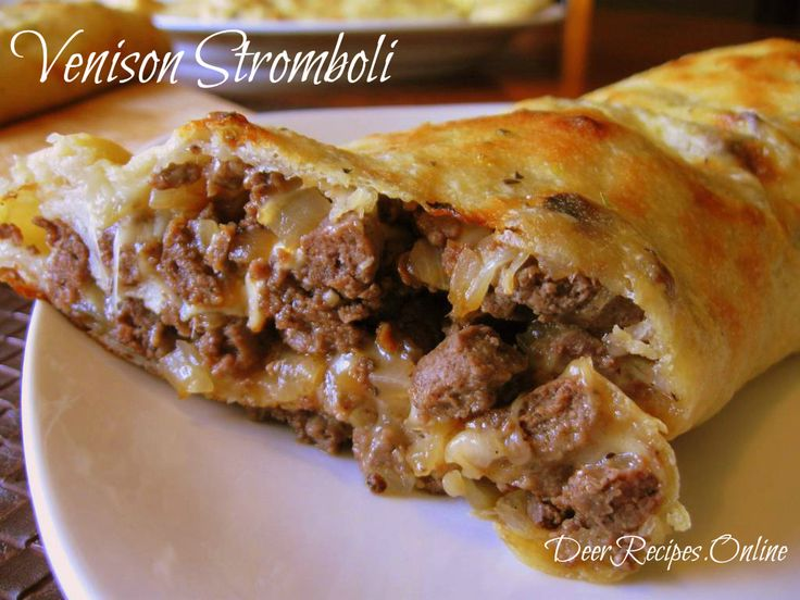 Venison Stromboli from Deer Recipes - Venison sausage crumbled and fried with onions and wrapped in a layer of thin pizza crust and mozzarella cheese and then brushed with butter and sprinkled with oregano and basil.#VenisonStromboli #Stromboli #EasyRecipes #Recipe #DeerRecipes #Venison #Sausage #Cheesy