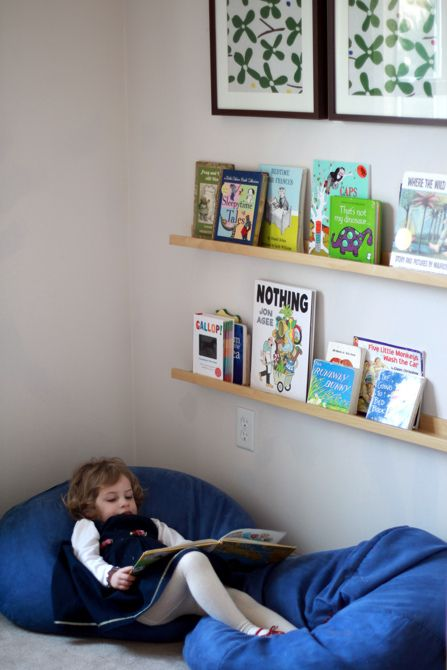 beanbags and front facing shelves for reading nook in room