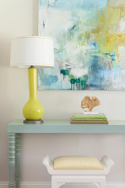 Yellow and blue foyer features a white stool tucked under a blue console table topped with a canary yellow lamp placed below a yellow and blue abstract art piece.