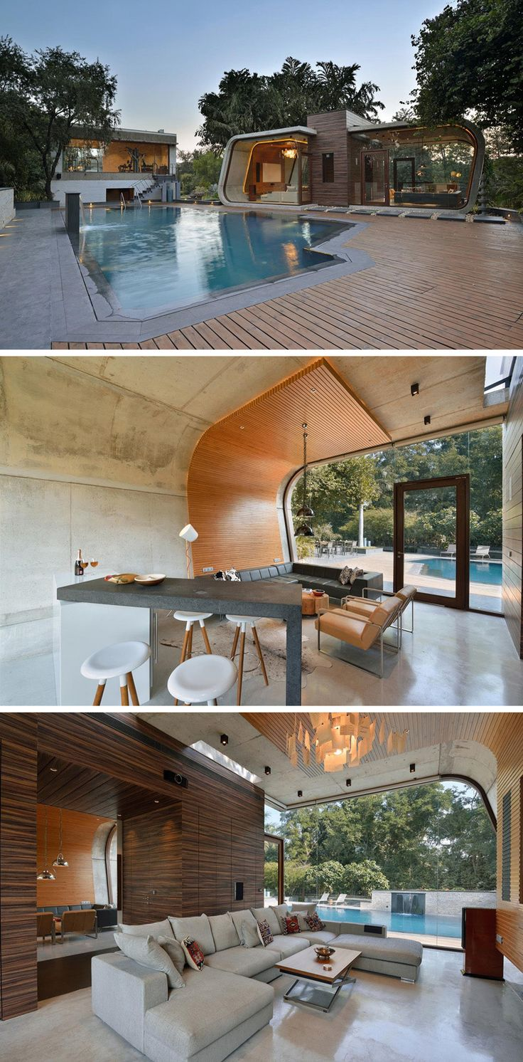 This curved concrete and wood pool house provides plenty of space to relax, and enjoy views of outside through the floor-to-ceiling windows.