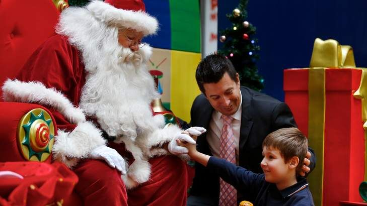 The 'sensitive santa' for kids with autism at Highpoint Shopping Centre in Maribyrnong with the centre manager Scott Crellin and his son Cooper. 9 December 2013.