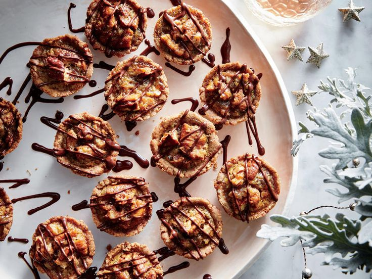 Think of these tasty little tassies as your own personal pecan pie. They're both salty and sweet, with a hit of oaky bourbon. Whole-grain rye flour adds the perfect touch of sour to the shortbread-like crust, while toasted pecans do double duty in the crust and in the maple-splashed filling. As if that weren't enough to jingle your bell, we drizzle warm bittersweet chocolate over each bite to ensure maximum satisfaction.
