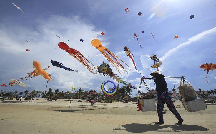 Durante el Festival Internacional de cometas, en la playa de Tam Thanh, ubicada en la provincia de Quang Nam, en Vietnam, un vendedor de comida camina debajo de ellas (AP)