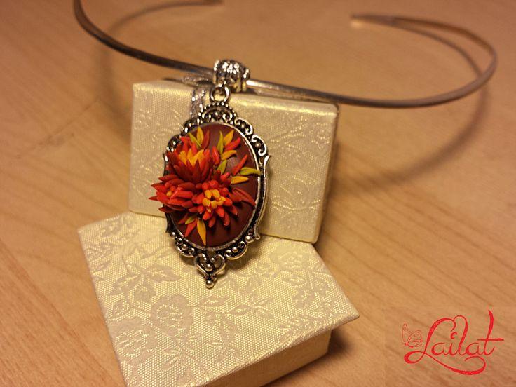 Un pandantiv  decorat cu un buchet de crizanteme în culori calde de toamnă, modelate manual din pasă polimerică.  Dimensiuni pandantiv: 5*2,5 cm.