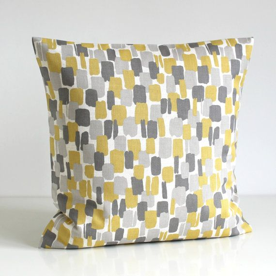 One pillow cover in trend colours of light mustard, dark grey and warm grey on an pale white background. A modern Scandinavian print on a beautiful