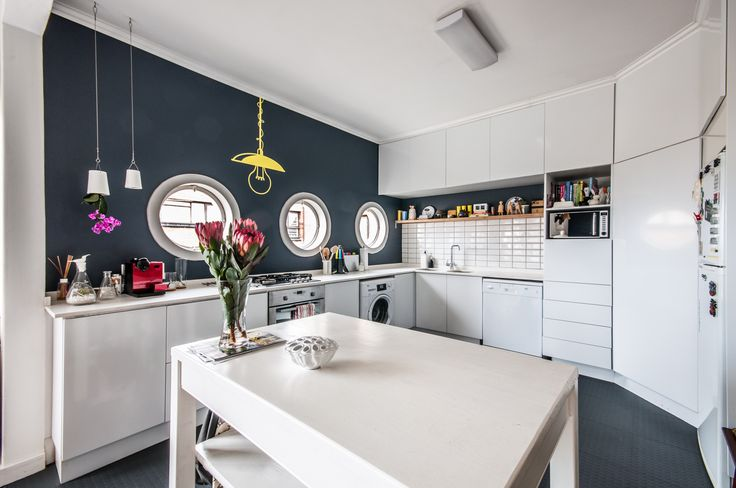 Kitchen in white with Plascon Dusk of Day painted wall with porthole windows #askasheabode