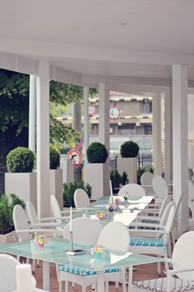White modern ensemble in italian style with coloured accents given by the plants and the chair pillows