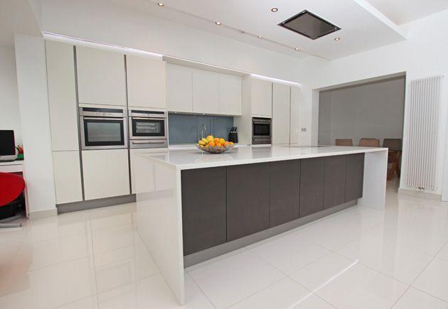 Large open plan kitchen island in Anthracite matt laminate with Glacier compac quartz worktop set against a run of white matt laminate doors.