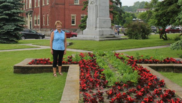 Teresa Glover has launched a nationwide movement to mark the 100th anniversary of the start of the First World War. Glover decided to email mayors across Canada, urging them to plant poppies in their town to  honour the  anniversary. To date, 85 towns and cities  – from Newfoundland to British Columbia – have notified her of their intention to participate in the initiative. Here in Port Hope she is photographed beside the poppies planted at the cenotaph in Memorial Park.