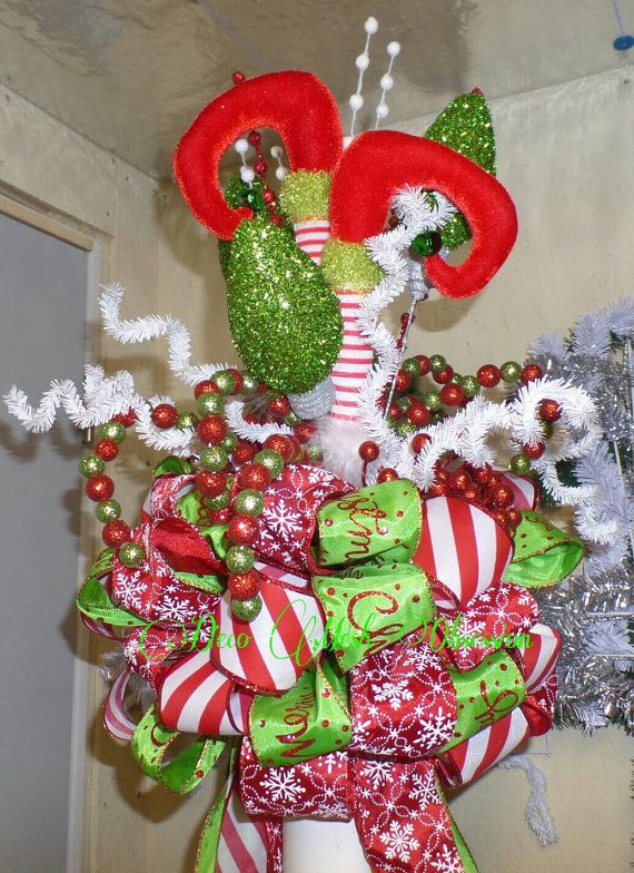 Here is my FAVORITE tree topper thus far!. This little Elf had a crash landing right into the top of your tree. The topper is made with whimsy elf legs and comes loaded with all sorts of candy pom poms, tinsel curls and glitter loops. It has wonderful red and white snowflake, red and white peppermint stripe and Merry Christmas ribbons. It would make the perfect addition to any tree and will last many seasons to come. Each topper is handcrafted and unique so If you would like this to be part…