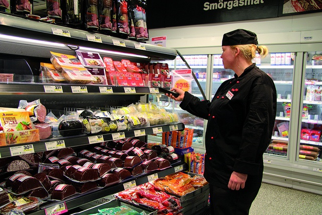 Store person making check ups, price checks, price markdown or taking stock with the Nordic ID Morphic mobile computer in a convenience store or a supermarket.