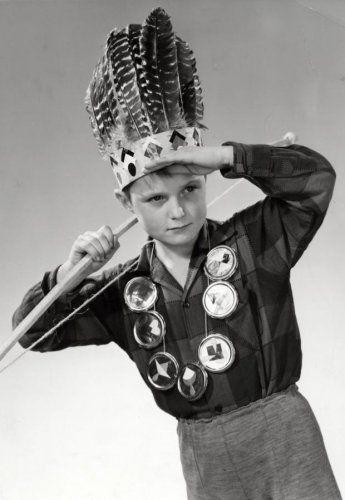 Peike Reintjens | Verklede kinderen. Jongetje met Indianen hoofdtooi en ketting van 'medailles' . Op zijn schouder een houten boog (pijlen ontbreken) Nederland 1957.