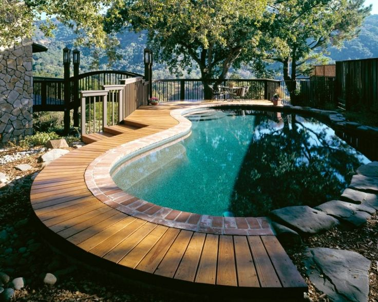geschwungene Form vom Schwimmbecken und Kombination von unterschiedlichen Materialien