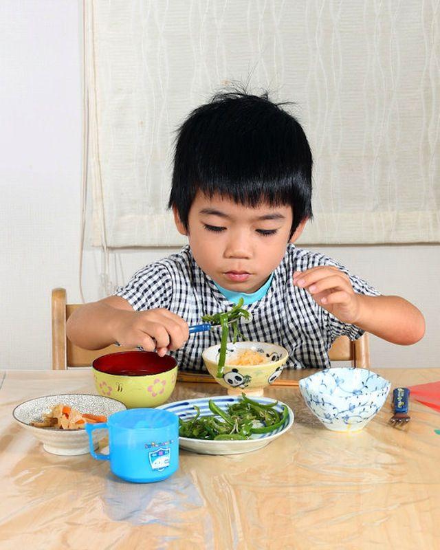 """Koki Hayashi, 4 años, Japón.A pesar de que muchas veces come un desayuno tradicional americano, su madre intenta darles comida tradicional japonesa. Desayuna chile verde frito con pescado seco, salsa de soya y semillas de sésamo; huevo revuelto con soya y con arroz hervido, algunas raíces y zanahorias salteadas con aceite de sésamo y un arroz dulce llamado """"mirin"""", junto con sopa miso, uvas, leche y pera asiática."""