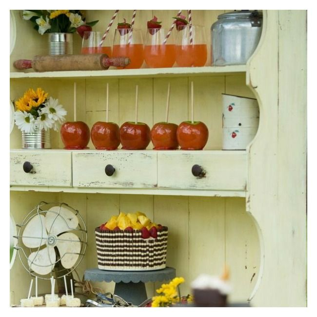 Vintage yellow distressed hutch dessert and drink display with candy apples, cake and vintage props