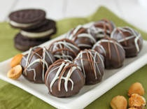 NUTELLA Oreo Balls!!: •1/2 cup toasted hazelnuts  •1 pound chocolate sandwich cookies (like Oreos)  •1/2 cup chocolate-hazelnut spread (like Nutella)  •6 ounces cream cheese, softened to room temperature  •12 ounces chocolate candy coating  •White or milk chocolate for drizzling (optional)