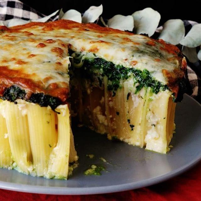 【アツアツを食べてね】チーズとほうれん草のマカロニケーキ ■材料 ・ほうれん草 250g ・ジェノベーゼペースト 大さじ1 ・リガトーニ 300g ・ピザチーズ 100g ・オリーブオイル 大さじ1 《カッテージクリーム》 ・カッテージチーズ 200g ・卵 2個 ・塩 小さじ1/3 《ホワイトソース》 ・鶏もも肉ひき肉 150g ・玉ねぎ 1/2個 ・バター 30g ・牛乳 100ml ・薄力粉 20g ・塩 小さじ1/2 ・白胡椒 少々 ■手順 【事前準備】 1)ほうれん草は茹でてフードプロセッサーにかけペーストにし、ジェノベーゼペーストと合わせる。 2)リガトーニは表示時間よりも2分短く茹で、ぬめりを軽く水で流す。 3)カッテージクリームの材料を合わせておく。 1. 底が取れるケーキ型の周りにアルミホイル巻き、リガトーニを立てて敷き詰めていく。カッテージクリームを流し入れ、隙間に埋めていく。 2. フライパンにバターを溶かし、鶏ももひき肉と玉ねぎいためる。玉ねぎがしんなりしたら、薄力粉を入れて全体にまぶし、牛乳と塩胡椒を加えて滑らかになるまで混ぜ合わせる。 3…