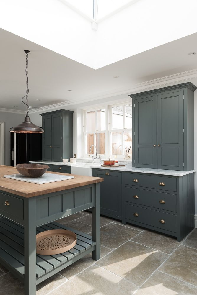 The Hampton Court Kitchen by deVOL painted in a beautiful bespoke paint colour with Umbrian Limestone flagstones throughout. Open end island unit