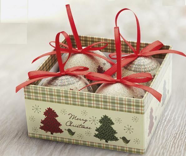 Set de 4 bolas de Navidad con acabado perlado y detalle de árboles rojos y verdes. Cinta de color rojo para colgar en el árbol. Presentado en caja de regalo a juego.