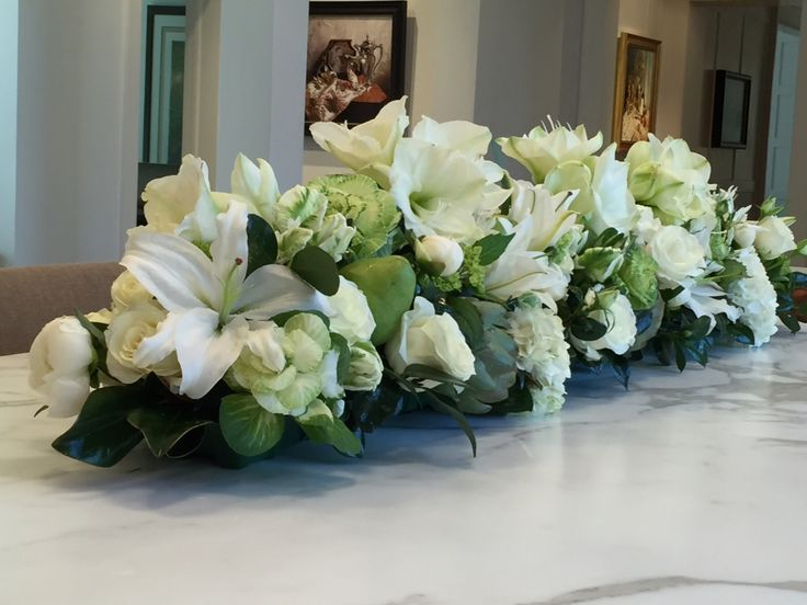 White and green long and low centerpiece with kale, parrot tulips, amaryllis, roses, peonies, magnolia, lilies, hydrangeas, pears and artichokes.