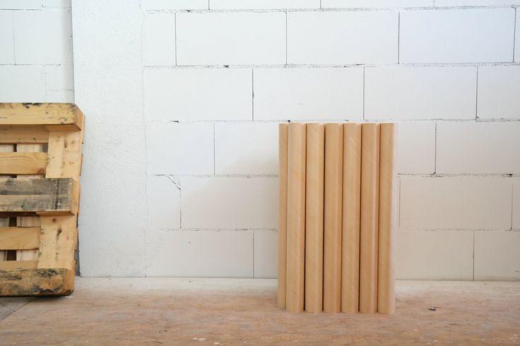 Stillleben: LignoTUBE Holzrohre und Palette vor weißer Wand.