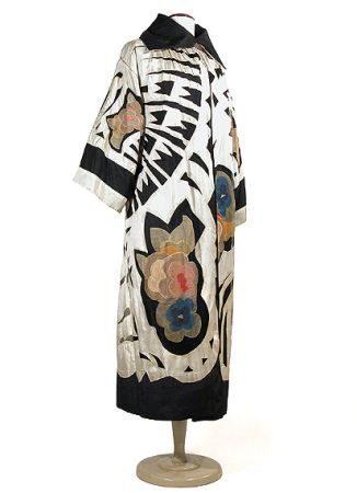 Dramatic Art Moderne Opera Coat   European, mid 1920s   The abstract and asymmetrical pattern of cutwork and applique primarily of creme china silk over black silk tulle with focal points of organdy applique floral clusters in various pastel shades, the sleeves applied with crochet stitch.