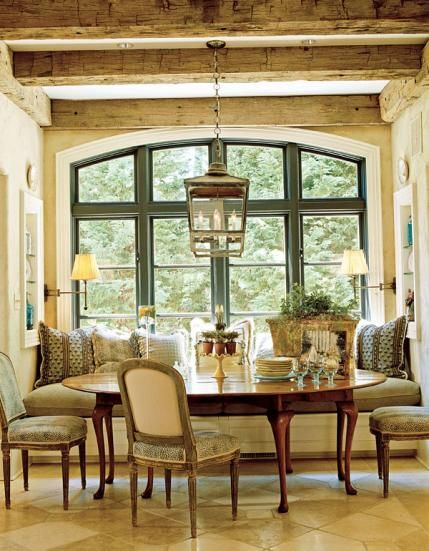 A roomy, pillow-fortified banquette nestles perfectly into the window bay in this breakfast area . - Traditional Home ® / Photo: Gordon Beall / Design Mary Jo Donohoe