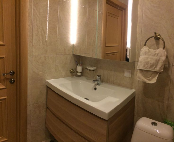 Интерьер ванной комнаты, раковина с подвесной тумбой, зеркало с подсветкой