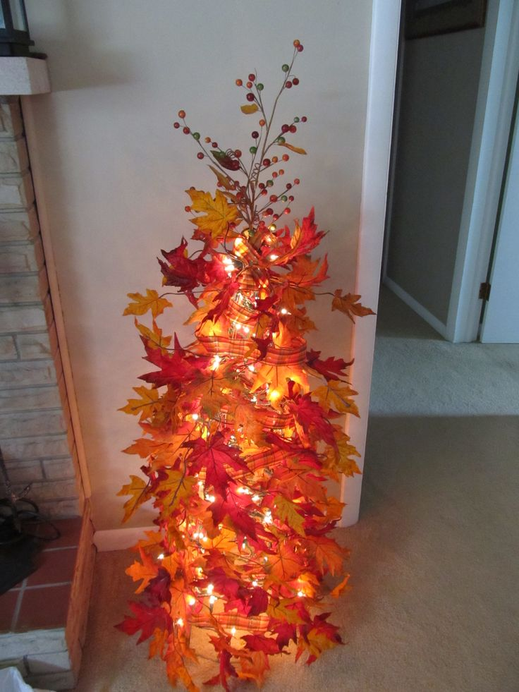 Made my own fall tree using a tomato cage, Christmas lights, fall garland, ribbon and a topper.  Easy to make and very pretty!