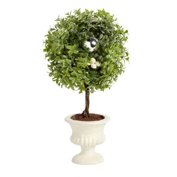 Adorned by shiny chrome ornaments and white berries, our boxwood tree is the perfect no-maintenance plant. This artificial topiary makes a lovely winter display.